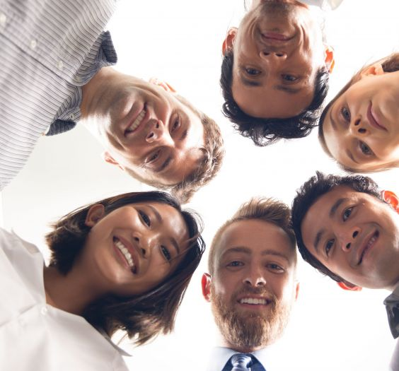 Closeup portrait of six smiling business people standing in circle and looking down at camera with their heads together. Bottom view.